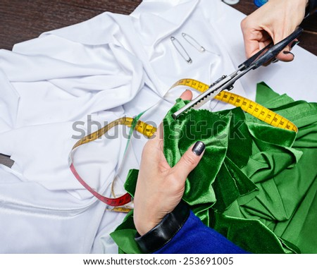 Woman cuts off a piece of fabric designer, hands shot close-up, a woman is not recognizable. - stock photo