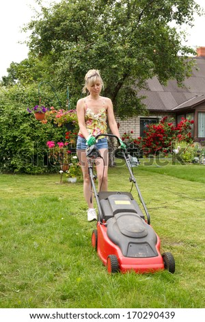 Woman cuts the grass with an electric lawn mower