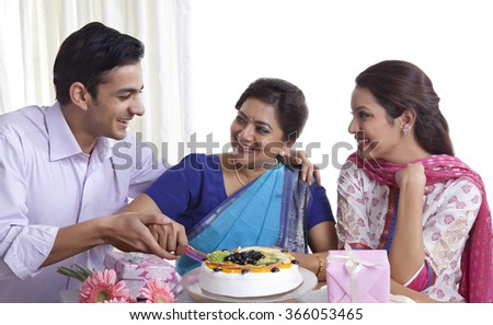 Woman cutting birthday cake with a knife - stock photo