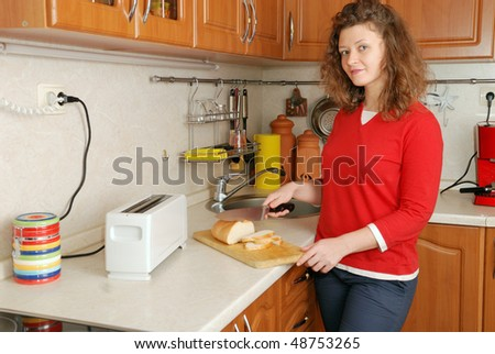 woman cutting bread at kitchen