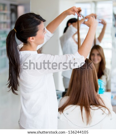 Woman cutting clients hair at the beauty salon - stock photo