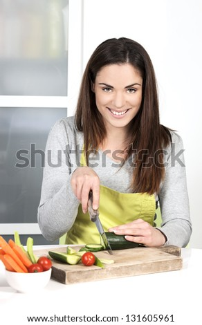 Woman cutting cucumber and in kitchen - stock photo