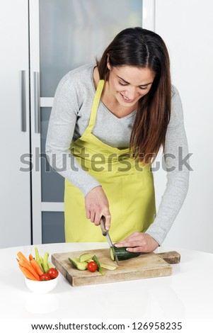 Woman cutting cucumber and vegetables - stock photo