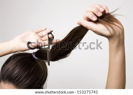 Woman cutting her ponytail - stock photo