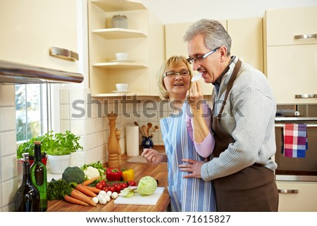 Woman cutting kohlrabi in the kitchen and man tasting it - stock photo