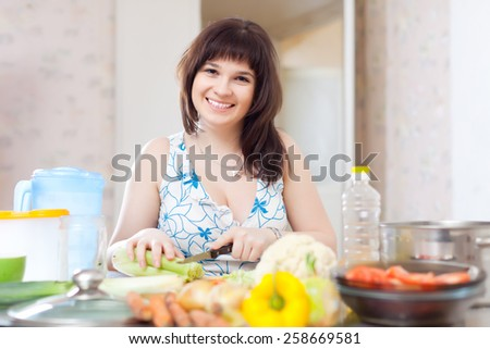 woman cutting the celery for salad in home kitchen