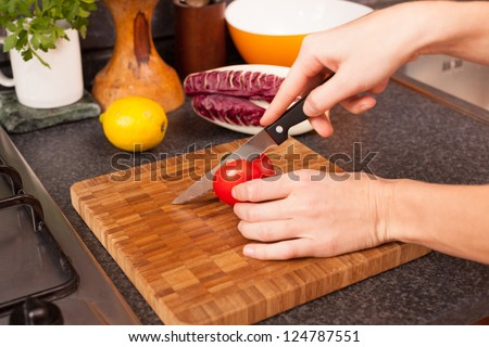 Woman Cutting Tomato in the Kitchen