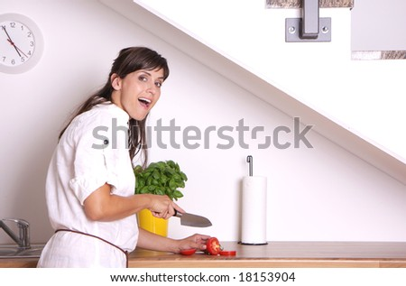 Woman cutting tomatoes slices in kitchen - stock photo
