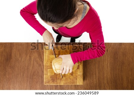 woman cutting up a loaf of bread taken from a birds eye view from above - stock photo