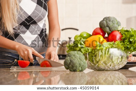 Woman cutting up tomato in kitchen for meal. Horizontal shot. - stock photo