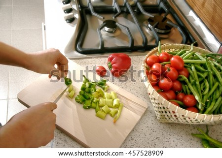 woman cutting vegetables in domestic kitchen