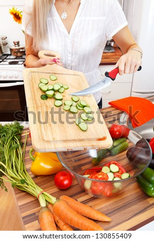 Woman cutting vegetables in the kitchen - stock photo