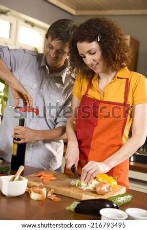 Woman cutting vegetables, man opening wine. - stock photo