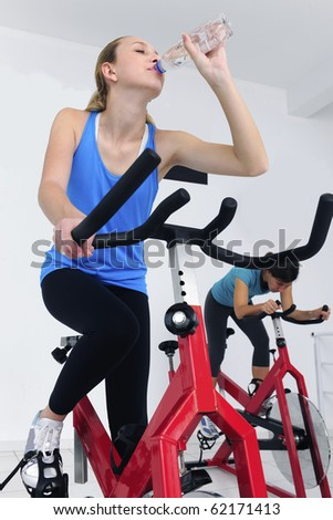 woman cycling at the gym and drinking water - stock photo