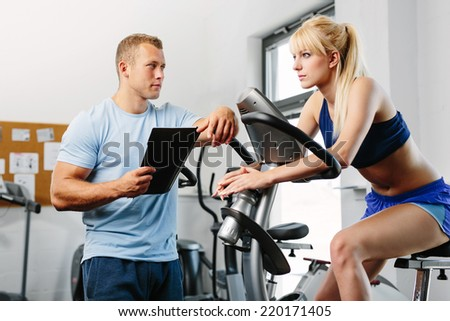 Woman cycling in a gym with personal trainer - stock photo