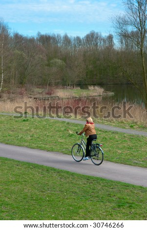 Woman cycling in a park along a lake. - stock photo