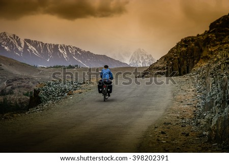 Woman cycling on a difficult mountain road towards Shandur Pass in northern Pakistan