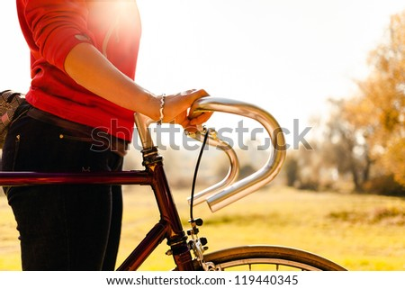 Woman cycling on bicycle, sunset autumn park exercising. Take a bike for a walk, vintage old retro bike, cycling or commuting in rural country environment, ecological transportation concept - stock photo