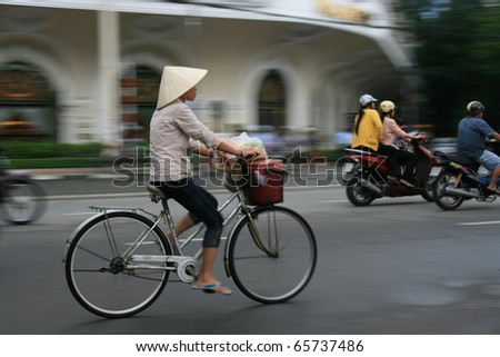 Woman cycling on busy Hanoi Roadwith traditional Vietnamese hat - stock photo