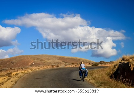 Woman cycling  on the grassland plateau in Madagascar