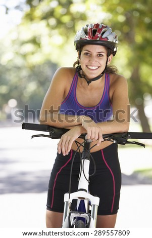 Woman Cycling Through Park