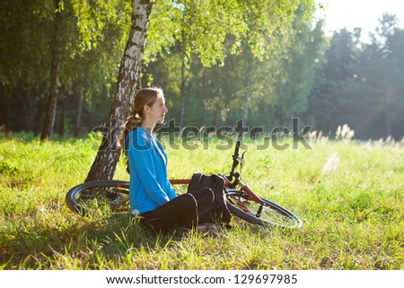 Woman cyclist enjoying relaxation in sunny park sitting in the fresh green grass