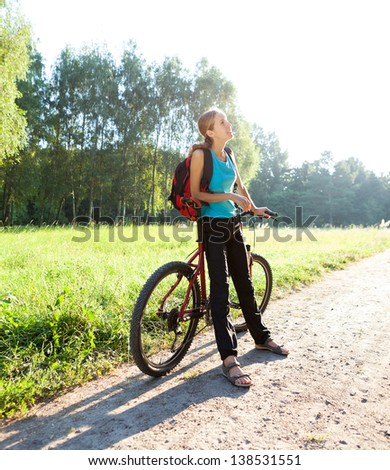 Woman cyclist on walking with bicycle in spring sunny nature. Outdoor - stock photo