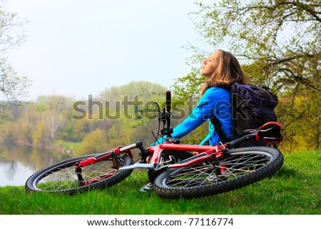 Woman cyclist relaxing, face to the sun's rays. At halt - stock photo