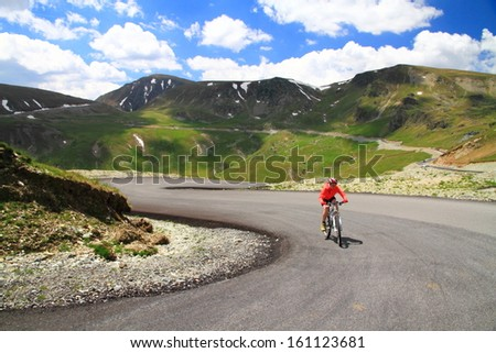 Woman cyclist training on a mountain road - stock photo