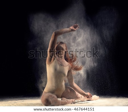 Woman dancer lying on the floor in a ballet pose with flour. Redheaded woman ballerina posing in beige bathing suit on a black background.