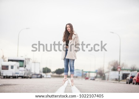 woman dancer on ballet tips, jeans and white coat on the street and look at camera