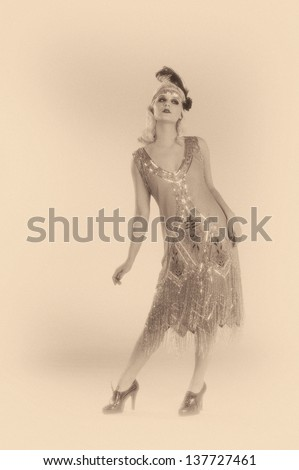 Woman dancing in a 1920's beaded flapper dress in sepia toned black and white. - stock photo