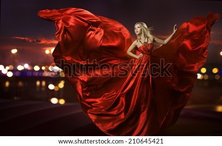 woman dancing in silk dress, artistic red blowing gown waving and flittering fabric, night city street lights - stock photo