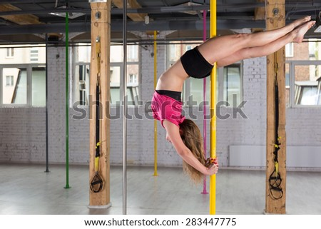 Woman dancing on the pole at the gym - stock photo