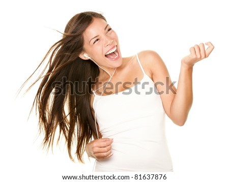 Woman dancing to music listening to mp3 player with earphones / earbuds. Energetic air guitar move by happy Asian / Caucasian dancer isolated on white background. - stock photo