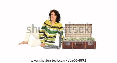 Woman Daydreaming sitting with laptop computer and vintage suitcase full of One hundred dollar bills isolated - stock photo