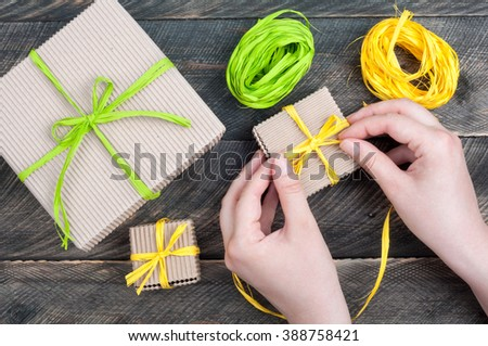 Woman decorates handmade gift boxes. Gift boxes on old wooden table. Top view - stock photo