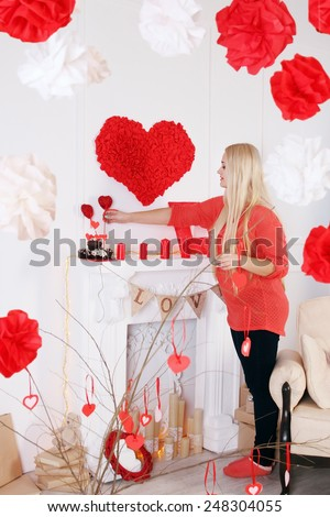 Woman decorates the house on Valentine's Day
