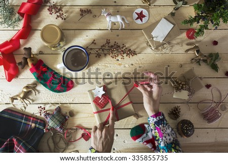 woman decorating a Christmas present with a branch of holly, Do-it-yourself Christmas decoration - stock photo