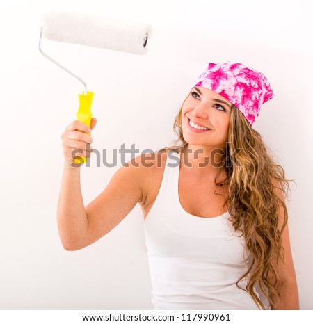 Woman decorating her house and holding a paint roller - stock photo