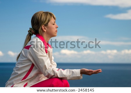 woman demonstrates yoga and meditation on beach - stock photo