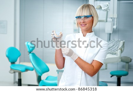 woman dentist holding dental model - stock photo
