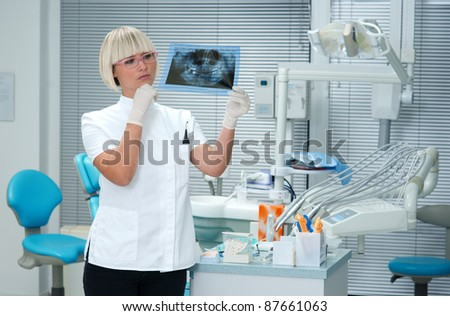 woman dentist looking at x-ray image of a human jaw - stock photo
