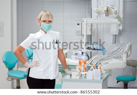 woman dentist standing in her office wearing mask - stock photo