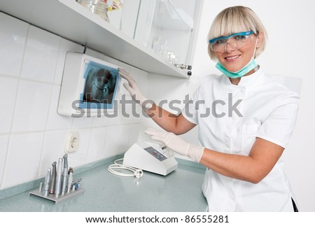 woman dentist with x-ray image smiling - stock photo