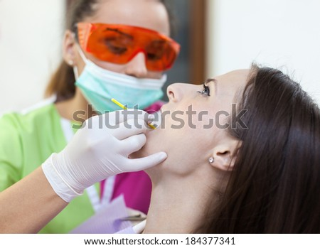 Woman dentist working at her patient's teeth