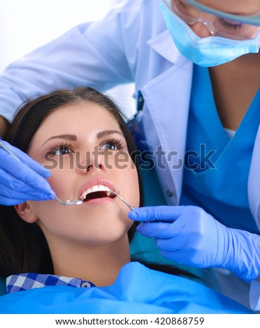 Woman dentist working at her patients teeth - stock photo