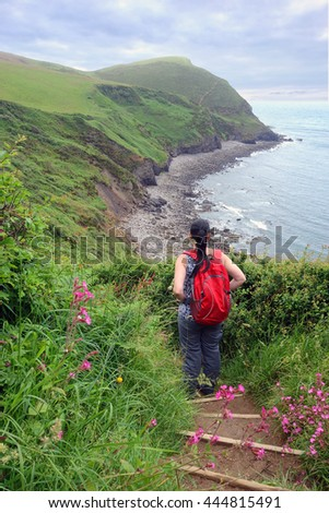 Woman descending the steps on the coastal path near Crackington Haven, Cornwall, England. - stock photo