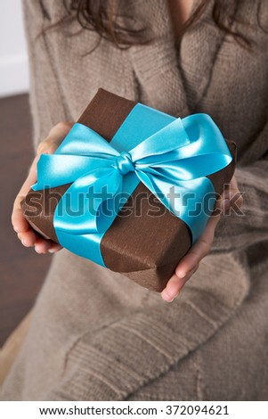 woman detail with a brown and blue gift box in her hands