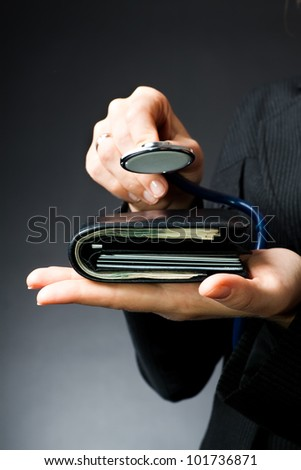 Woman diagnoses purse full of money and plastic cards (medical business background - medical insurance) - stock photo